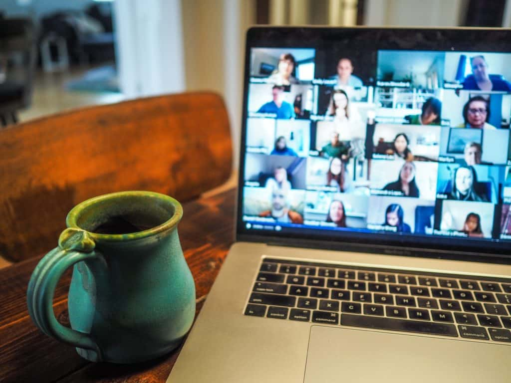laptop open with a grid-view of people having an online meeting