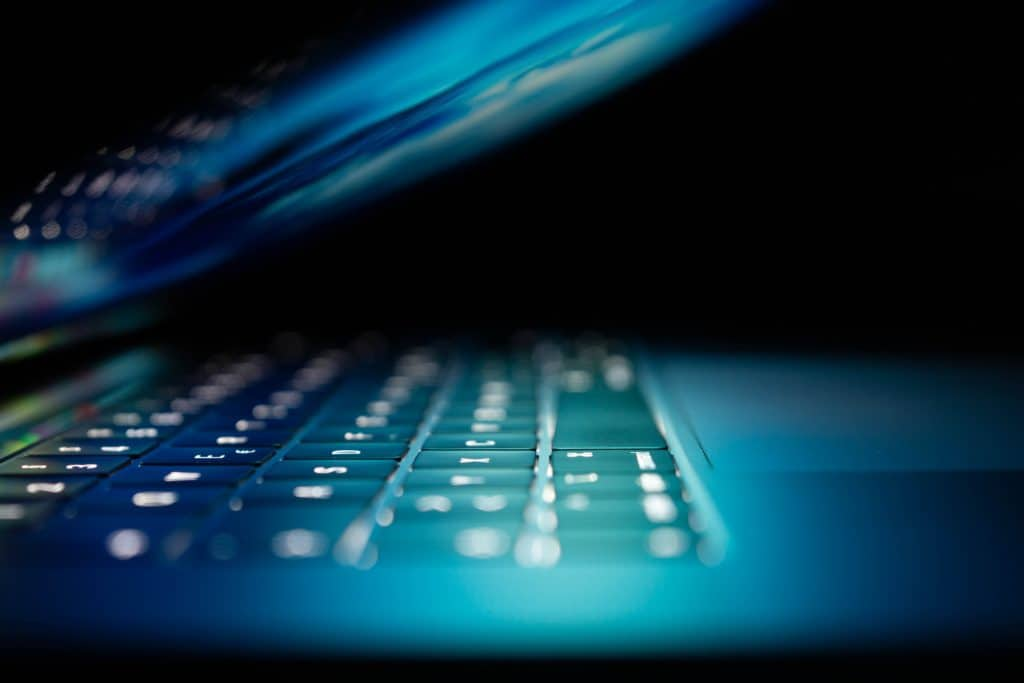 dark laptop open with lighted keys